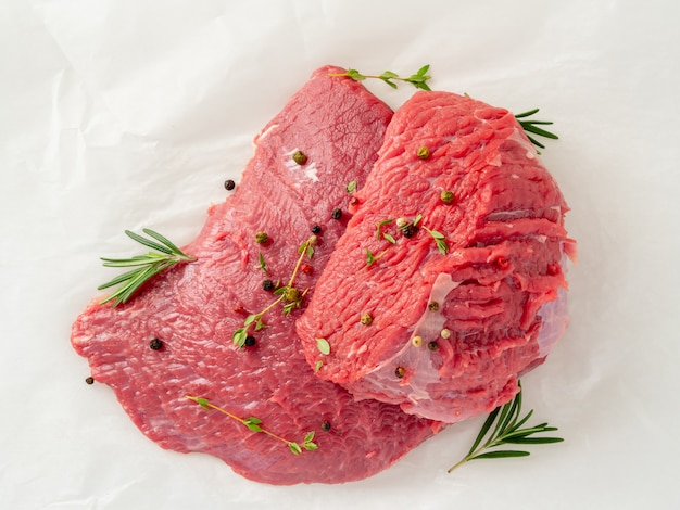 調味用ローズマリー、白い羊皮紙紙の上のコショウ、生の牛肉