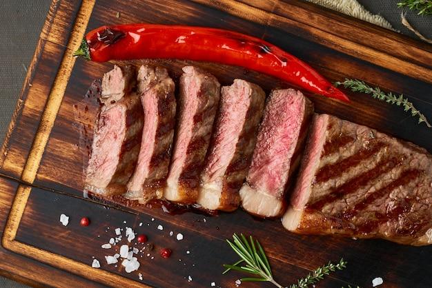 ケトケトジェニックダイエットビーフステーキ、まな板の上のストリップロインのグリル。パレオフードレシピ