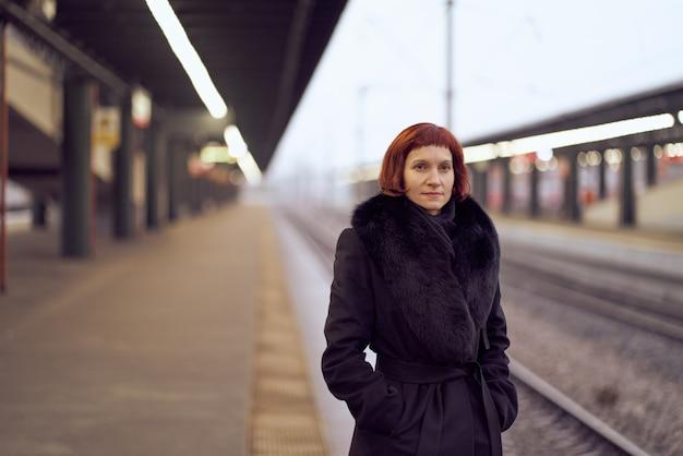 鉄道駅。美しい少女はプラットフォームに立って、電車を待っています