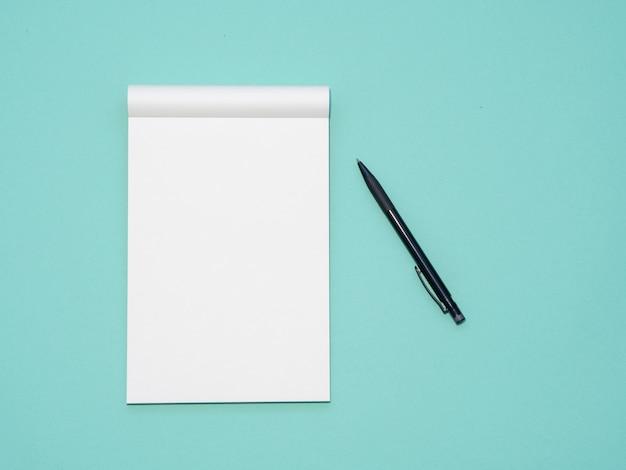 ノートブックを開くとペンとアクアの背景上のトップビューワークスペースモックアップ