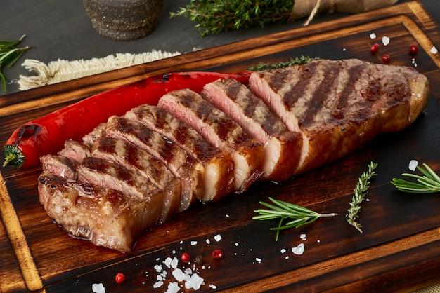 ケトケトジェニックダイエットミディアムビーフステーキ、まな板の上のグリルストリップロイン。肉と古食のレシピ