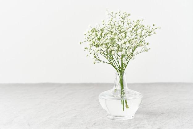 Гипсофила цветы в стеклянной вазе. мягкий свет, скандинавский минимализм,