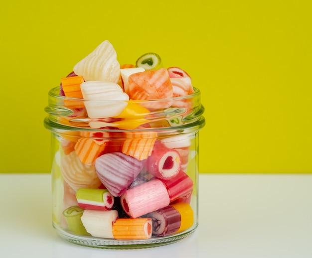 白いテーブルの上の壁のオリーブ色に対してガラスの瓶に着色されたお菓子