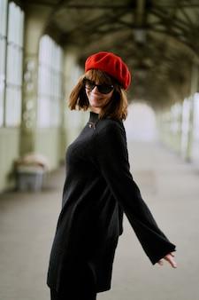駅で踊る美しい面白いいたずらスタイリッシュなおしゃれな幸せな女。魅力的な笑顔