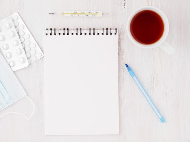 Откройте блокнот с пустой страницей, чтобы написать лечение. пилюльки, термометр на белой предпосылке, взгляд сверху.