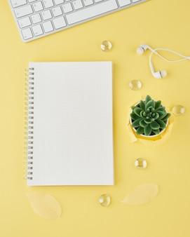 明るい黄色のオフィスのデスクトップの弾丸ジャーナルの空白のメモ帳ページ。