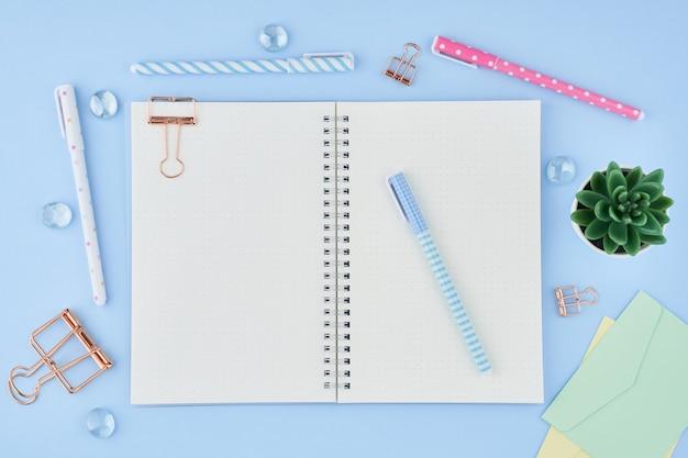 明るい青いオフィスのデスクトップの弾丸ジャーナルの空白のメモ帳ページ。