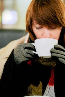 Замороженная женщина греется горячим напитком.