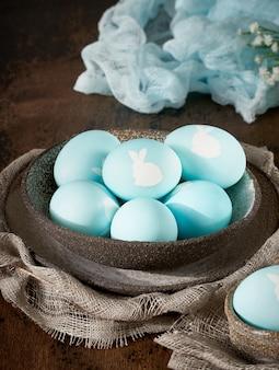 暗い古い背景に珍しいイースター。青い卵とセラミックの茶色のボウル。闇、日光