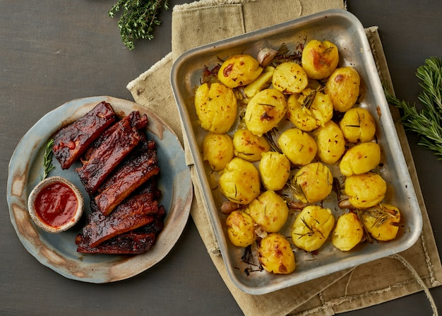 バーベキューの豚カルビと砕いた砕いたジャガイモ。スロークッキングのレシピ。