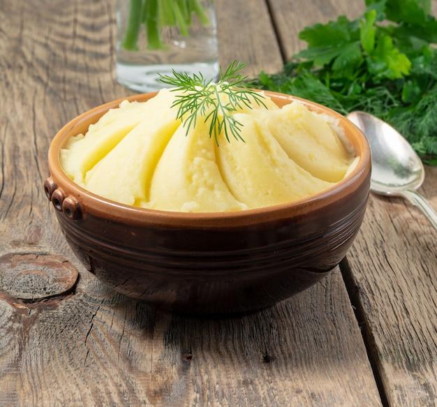マッシュポテト、素朴な暗い背景の木、側面に茶色のボウルに煮ピューレ