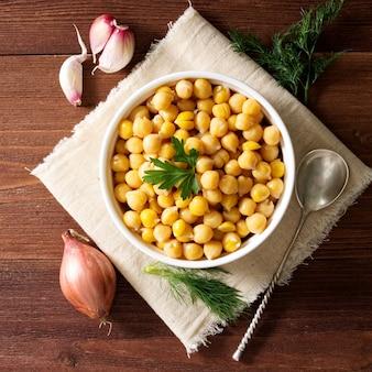 暗い木製のテーブルの上にボウルに調理されたひよこ豆。健康、菜食主義
