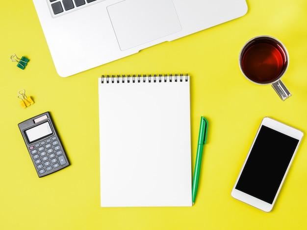現代の創造的な明るい黄色の事務机、ラップトップ、スマートフォン