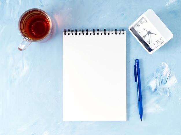 メモ帳、モックアップ、空スペースでモダンな明るい青いオフィスデスクトップの平面図です。