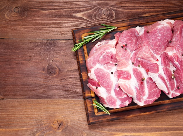 生豚ロース肉は、暗い背景の木、上面、コピー領域のまな板の上をチョップします。