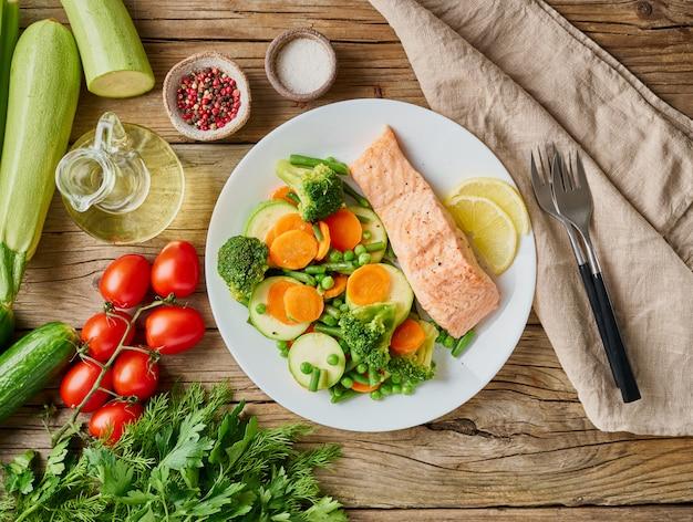 スチームサーモンと野菜、パレオ、ケト、フォッドマップダイエット、古い素朴な木製のテーブル、トップビュー