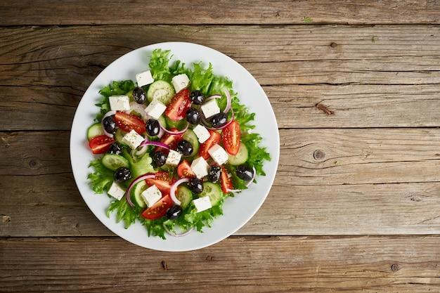 古い素朴な木製のテーブル、上面図、コピースペースに白い皿の上のギリシャ風サラダ