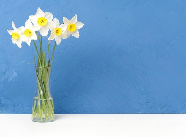 新鮮な花の花束、白いテーブル、青い壁にガラスの花瓶と水仙