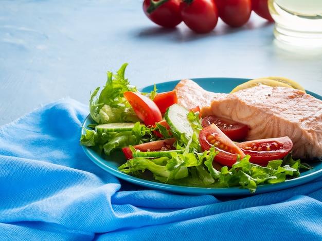 スチームサーモンと野菜、パレオ、ケト、フォッドマップダイエット。青いテーブルの上の青いプレート、側面図