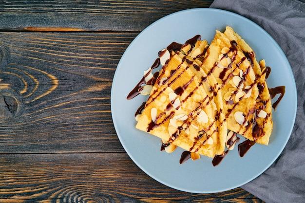 Два блина с шоколадным сиропом, миндальными хлопьями на тарелке, медом