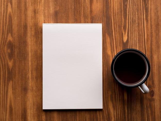 ティーカップと木製のテーブル、上面のきれいな白いページとメモ帳を開く