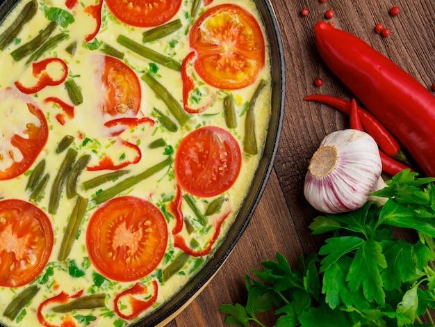 スクランブルエッグ、トマトおよび他の野菜が付いている鋳鉄鍋の一部。