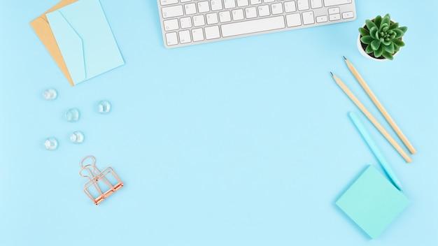 バナーブルーオフィスデスクトップ。事務用品、キーボードとモダンな明るいテーブルの平面図です。モックアップ
