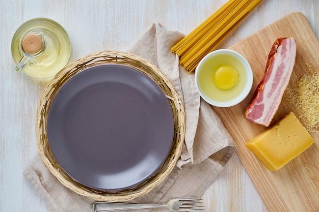 カルボナーラパスタレシピの材料 - スパゲッティ、ベーコン、卵、パルメザンチーズ、空の皿。