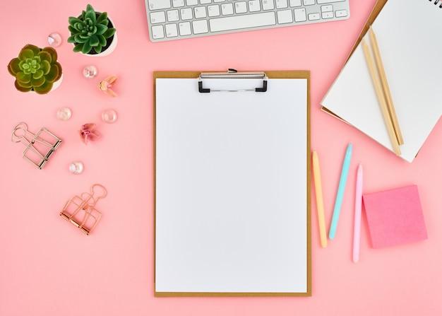 ピンクのオフィスのデスクトップ上のテキストの空白のメモ帳ページ。