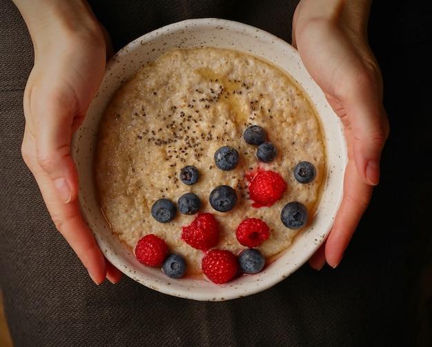 ダークフードの写真。暗い背景、上面に手でお粥とプレート。健康的な朝食