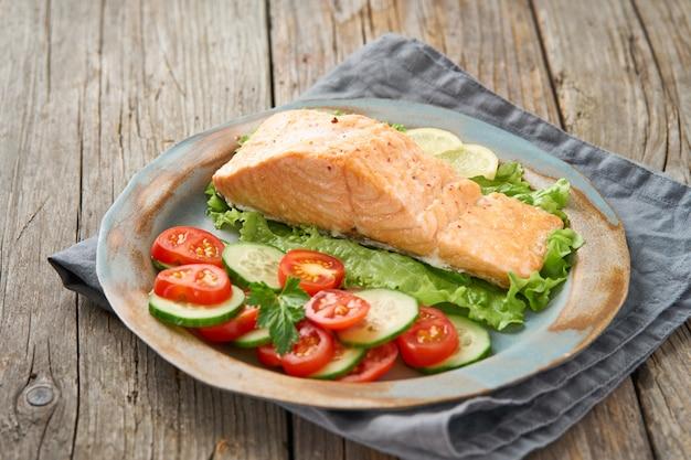 スチームサーモンと野菜、パレオ、ケト、フォッドマップダイエット。側面図。健康的な食事のコンセプト、ブループレート