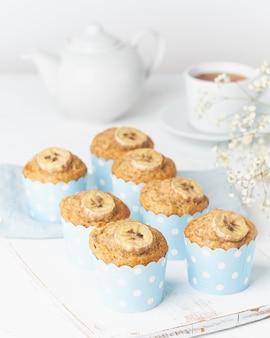 バナナマフィン、青いケーキケース紙のカップケーキ、白いコンクリートのテーブル