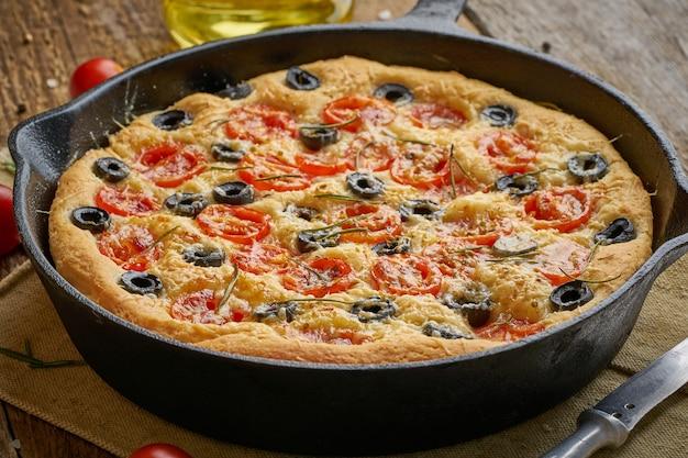 フォカッチャ、フライパンでピザ。トマト、オリーブ、ローズマリーとイタリアの平らなパンを閉じる
