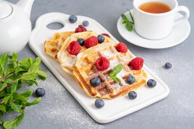 ラズベリー、ブルーベリー、紅茶、サイドビューのベルギーワッフル。健康的な自家製の朝食