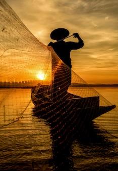 Рыбак в действии при ловле на озеро, таиланд
