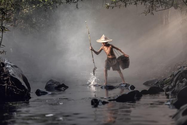 小川で釣りをする少年