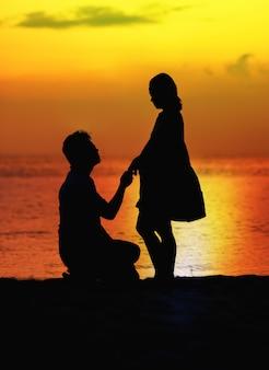 妊娠中のカップル、ビーチで夕日のシルエット