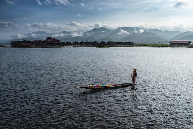 ミャンマーのインレー湖にあるインデインコーン村のボートに乗って手作りのカラフルな蓮の布を着た女性。