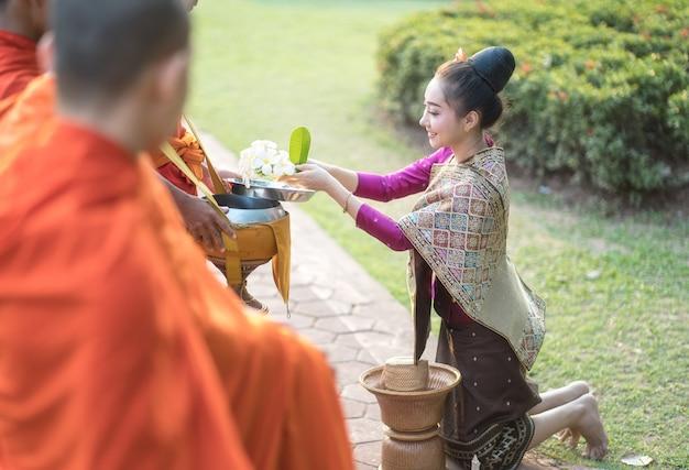 Женщина в традиционной одежде сидит, молится, уважает монаха, представляет буддизму людей. сделайте заслугу монаху тому представителю будды. женщина зарабатывайте, предлагая еду монаху.