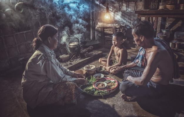 タイの家族が一緒に家で食事を楽しんで、タイの田舎