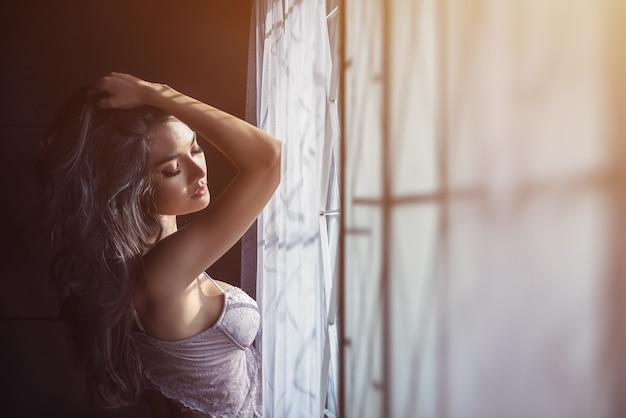 下着の窓の近くのセクシーな女性の肖像画。窓の近くでリラックス