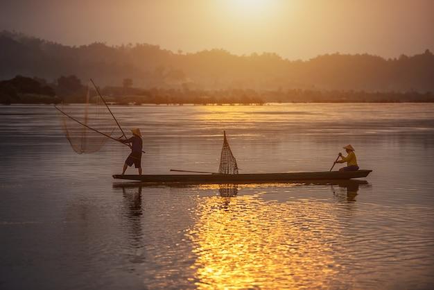 タイの田舎で日の出の背景に漁師