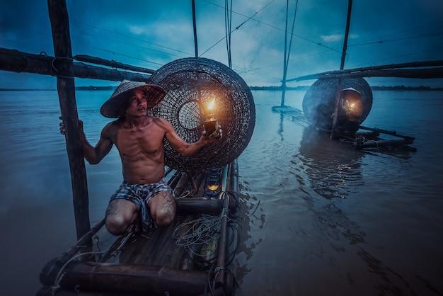 メコン川で釣りをするのを待っているボートにランタンを持っているアジアの漁師。夕暮れの間
