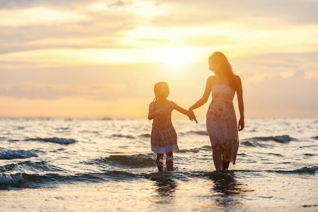 母と娘が遊んで遊んで、夕日のビーチで遊ぶ