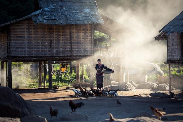 ラオスの田舎で鶏を食べるアジアの女の子