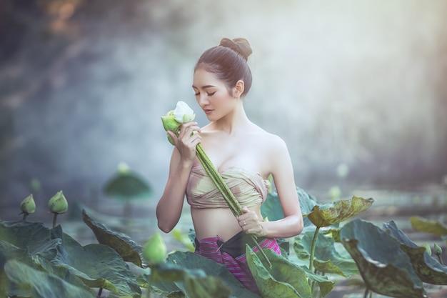 アジアの女性は、庭、タイで蓮の花を収穫します。