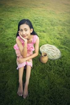 タイの地元の女性、草原、タイに座って