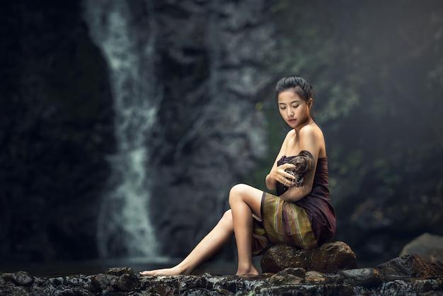 美しい若い女性は自然の中で風呂を取る