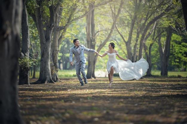 花嫁と新郎が走って公園にいて手をつかむ