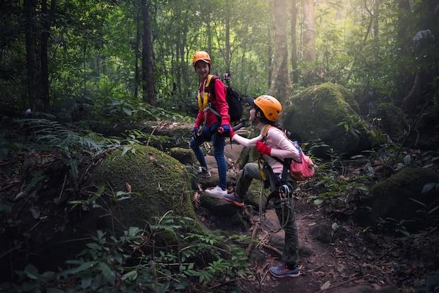 チームワークのカップルハイキングは、お互いに信頼の支援を助けます
